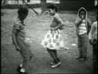 1960s medium shot Black boy and girl dancing outdoors / others in background