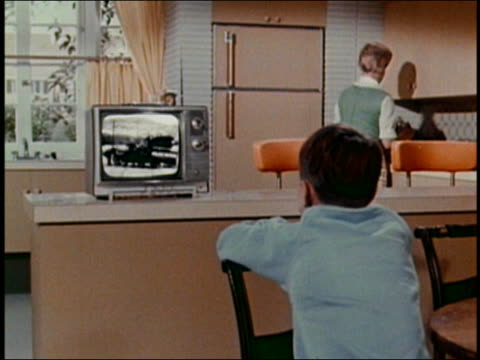 1960s medium shot boy watching television on kitchen counter w/mother in background / AUDIO