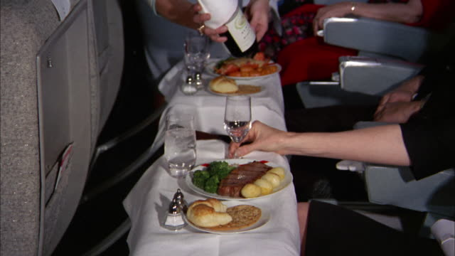 1960s medium shot first class airplane meals on white tablecloths / zoom in red wine being poured in glass