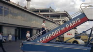 1960s medium shot flight crew walking up steps to board plane at Aeroport de Paris / Paris, France
