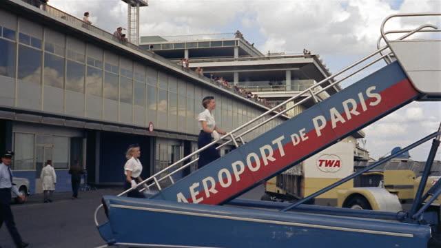 1960s medium shot flight crew walking up steps to board plane at Aeroport de Paris / Paris, France