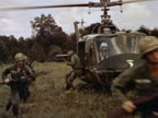1960s medium shot pan US soldiers climb out of helicopter holding guns / running across field / Vietnam