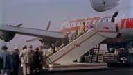 1960s medium shot passengers climbing stairs to board airplane