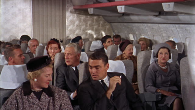 1960s medium shot passengers talking and smoking on 707 plane / flight attendant walking through aisle