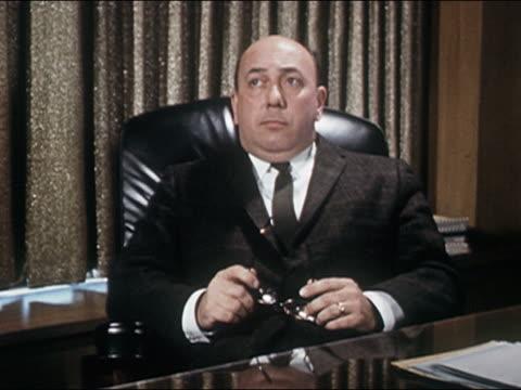 1960s medium shot REENACTMENT businessman removing glasses while contemplating at desk
