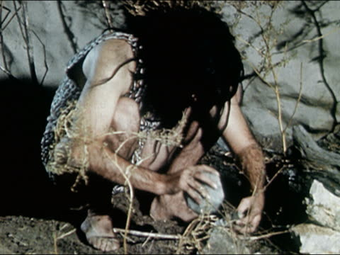 1960s medium shot reenactment caveman banging together rocks and hurting finger / grabbing club when startled