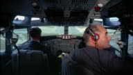 1960s medium shot three pilots w/headsets in jet plane cockpit during approach and landing