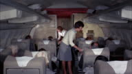 1960s medium shot two flight attendants serving champagne to first class passengers on airplane
