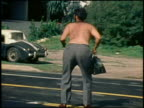 1960s medium shot zoom in shirtless man shaking buttocks at CAM while standing in middle of street / California