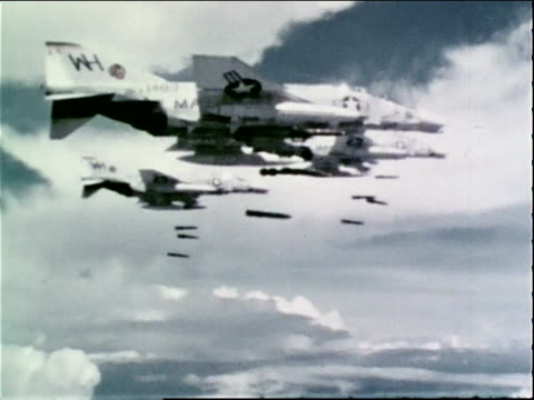 1960s MONTAGE a squadron of fighterbombers dropping bombs / Vietnam