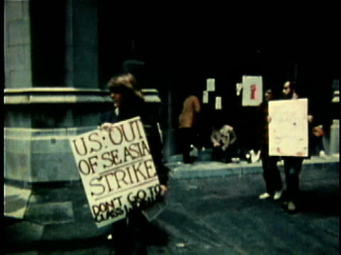 1960s MONTAGE Group of protestors walking in picket line holding antiVietnam War placards / United States