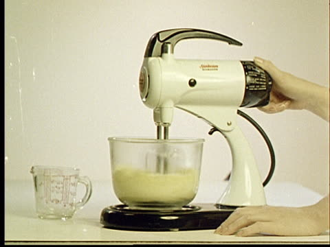 1960s MONTAGE CU Hand holding electric mixer / CU Mixing bowl rotating as beaters turn