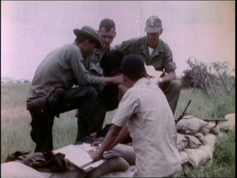 1960s MONTAGE soldiers interrogating blindfolded POW / Vietnam