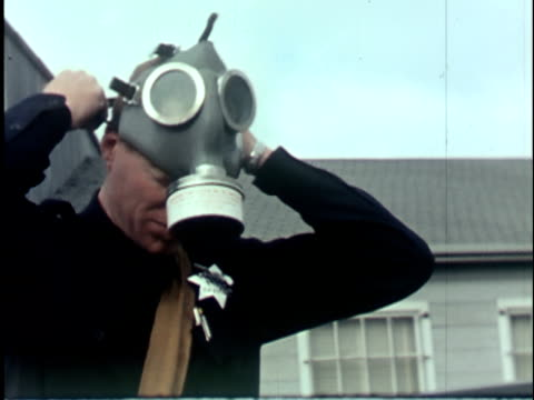 CU 1960s Police officer putting on gas mask, California / USA