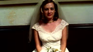 1960s REENACTMENT MS bride sitting holding bouquet inside church