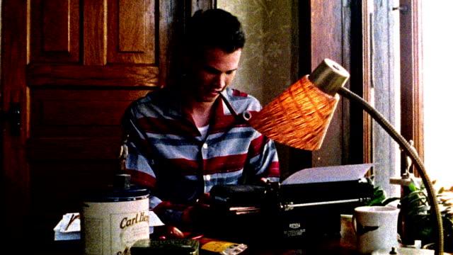 1960s REENACTMENT MS man in striped shirt smoking pipe, smiling, + typing