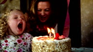 1960s REENACTMENT slow motion close up girl blowing at birthday cake candles / woman leaning over to help