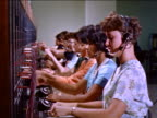 1960s row of female switchboard operators / educational