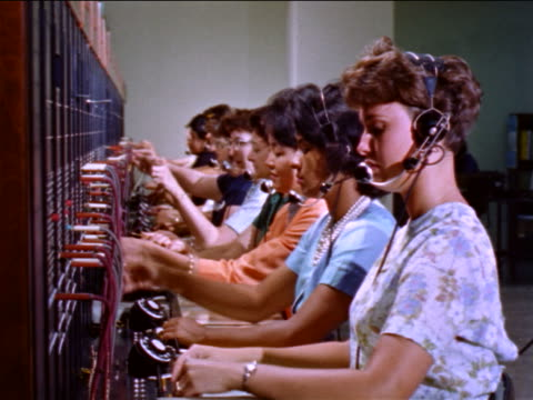 1960s row of female switchboard operators / educational