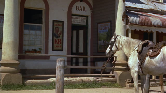 1960s MS Saddle horse tied to rail in front of bar