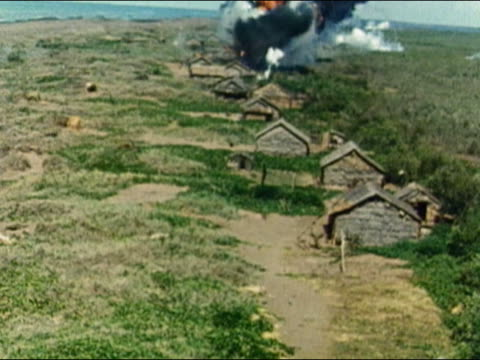 1960s slow motion aerial wide shot succession of napalm bombs exploding over country village / Vietnam