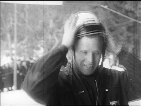 B/W 1960s smiling winner of toboggan competition removing helmet / Villach Austria / educational