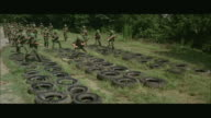 1960s WS Soldiers running through tires during obstacle course at army camp