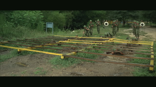 1960s WS Soldiers training on obstacle course at army camp, crawling under low bars