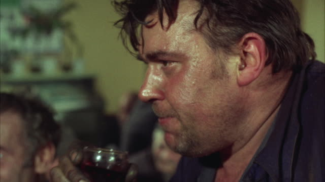 1960s CU Sweating man drinking from glass