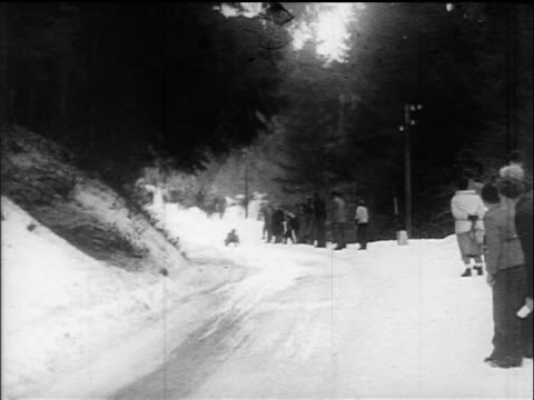 B/W 1960s PAN tobogganer coming down run quickly / Villach Austria / educational