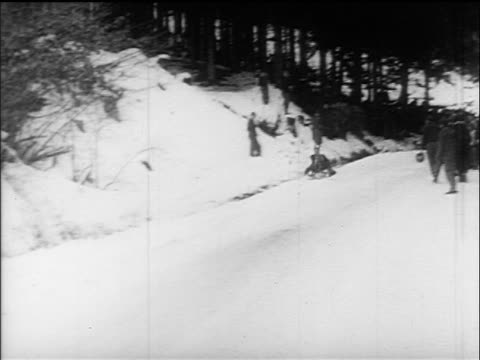 B/W 1960s PAN tobogganer coming down slope quickly past camera / Villach Austria / educational
