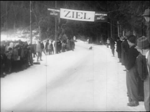 B/W 1960s PAN tobogganer going past finish line / Villach Austria / educational
