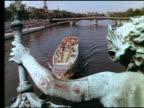 1960s tour boat on Seine River / tilt up Pont des Invalides + Eiffel Tower in background / statue in foreground / Paris