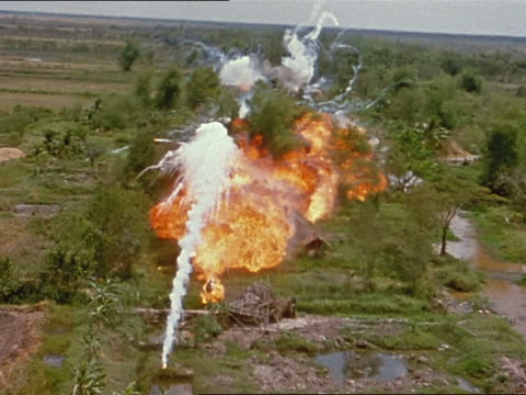 1960s Vietnam War rear plane point of view US plane dropping white phosphorus and napalm on village / Vietnam