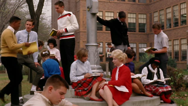 1960s wide shot male and female students discussing school work outside high school