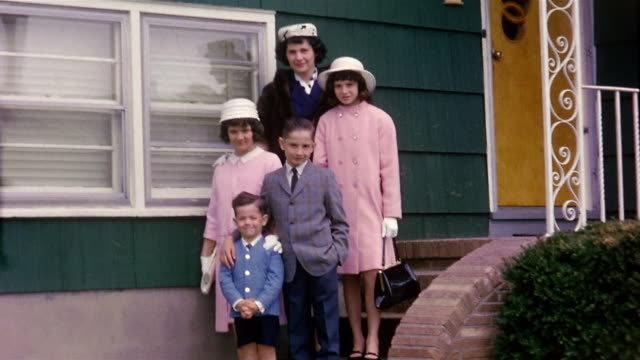 1960s wide shot mother and four children in formalwear standing on doorsteps of house / walking toward CAM