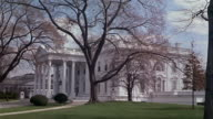 1960s wide shot side view of the White House and gardens / Washington DC