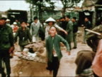 1960s wide shot Vietnamese civilians and soldiers carrying wounded person on stretcher / Vietnam War / AUDIO