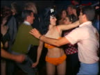 1960s woman in orange fringed bikini dancing with man amongst crowd indoors