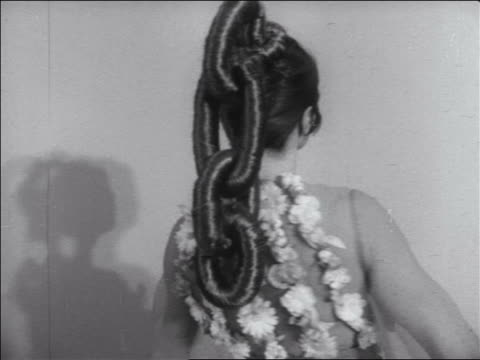 B/W 1960s woman with hair in chain link ponytail + Jacques Esterell dress turning to camera / newsreel