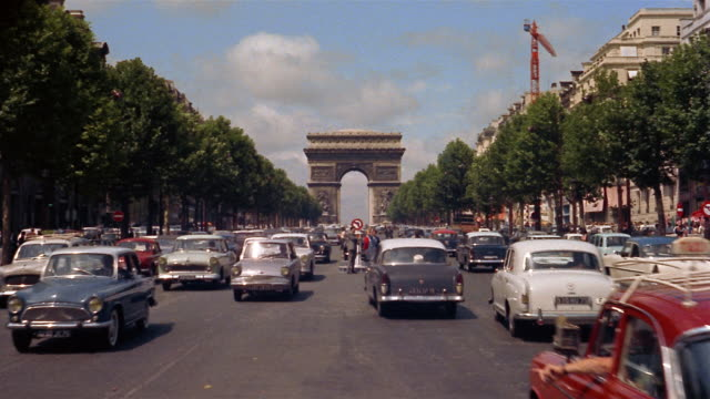 1960s/70s long shot traffic on the Champs-Elysees with Arc de Triomphe in background / Paris, France