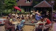 1960s/70s medium shot man and woman performing folk dance outdoors for audience seated at tables