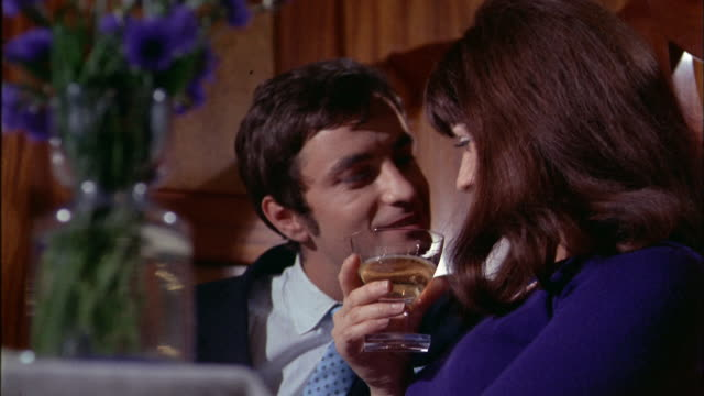 1970s close up man and woman drinking champagne in restaurant / man trying to kiss woman