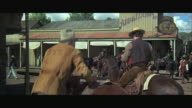 1970s WS Group of men on horseback ridding up to saloon