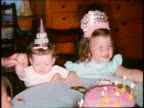 1970s HOME MOVIE small girl + baby in party hats sitting at table with birthday cake / waving