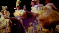 1970s low angle wide shot dancers doing splits and performing Cancan on stage at Moulin Rouge / Paris