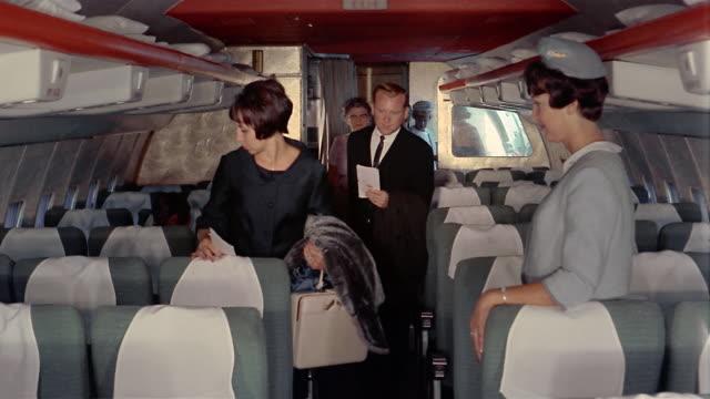 1970s medium shot passengers boarding airplane and taking their seats