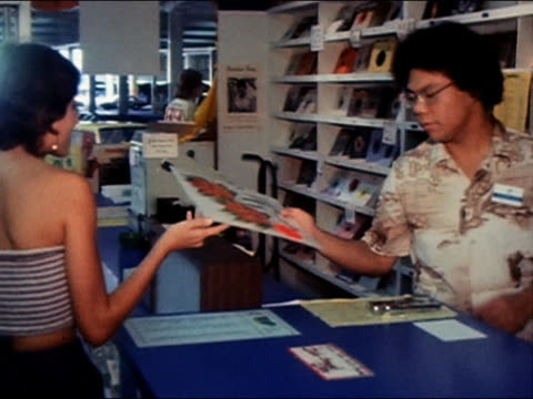 1970s medium shot tracking shot young woman bringing album to counter / zoom out tilt down buying album in record shop / Hawaii