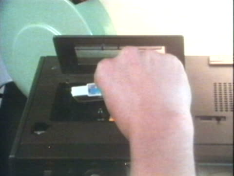 1970s MONTAGE CU Hand inserting tape cassette into tape player and turning volume dial / AUDIO
