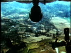 1970s MS SLO MO Napalm bombs dropping from US bomber plane over countyrside during the Vietnam War / Vietnam